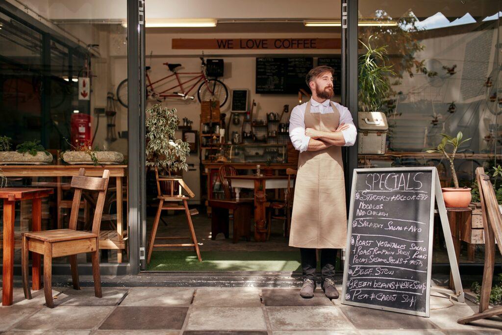Mann in Schürze vor Café mit Werkstatt