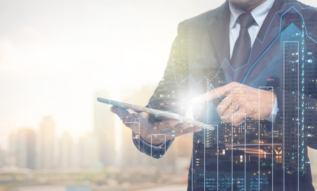 Double Exposure Of Businessman Using The Tablet With Cityscape