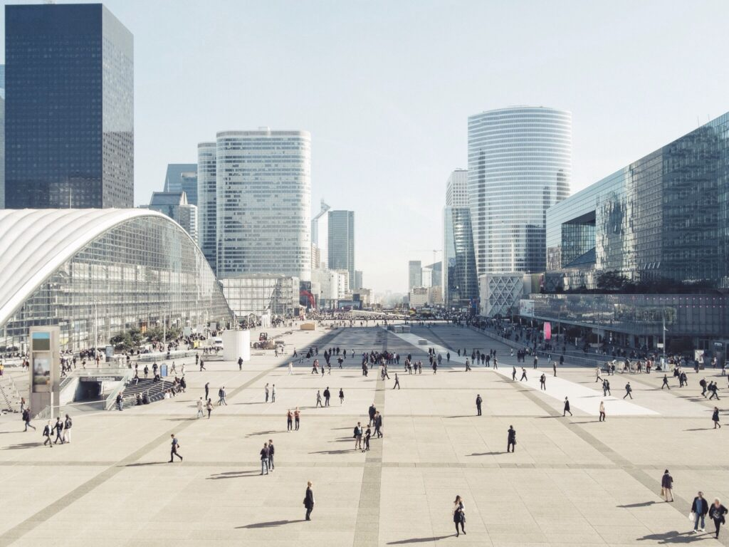 High Angle View Of People On Street Amidst Modern Buildings Against Clear Sky